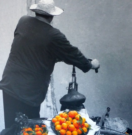 Photo of man on bike with oranges