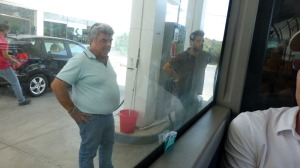 Our driver (left) watches while our attendant mans the pump. Photo taken from inside the bus.