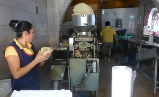 The tortilla machine. The glop at the top is simply ground corn and water.  Tortillas come out the other end.