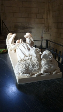 Sheep and angels guard a burial crypt in St. Ours